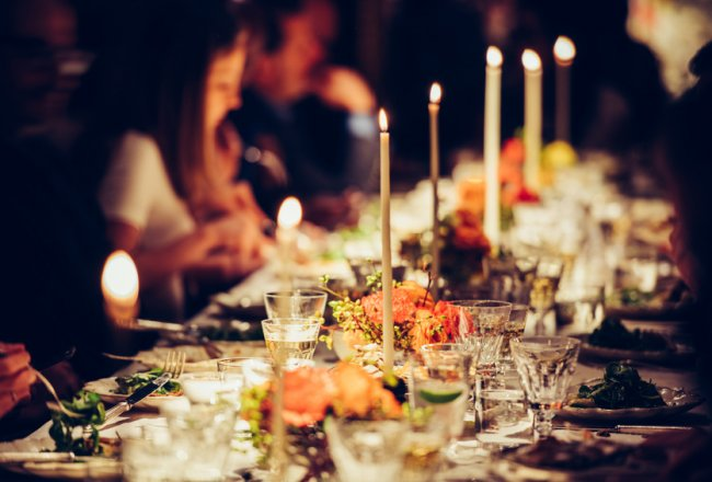 People enjoy a family dinner with candles. Big table served with food and beverages.